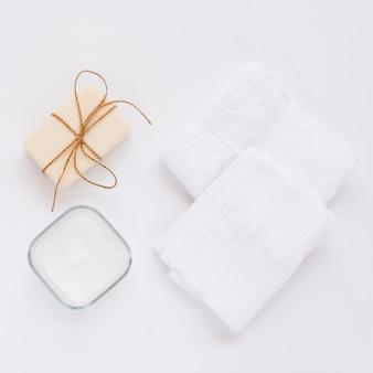 Vista superior de la mantequilla corporal y jabón sobre fondo liso