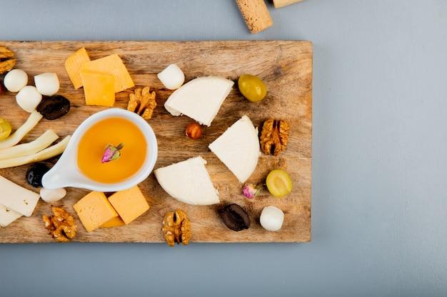 Vista superior de mantequilla derretida con diferentes tipos de queso uva nueces de oliva en la tabla de cortar en blanco con espacio de copia