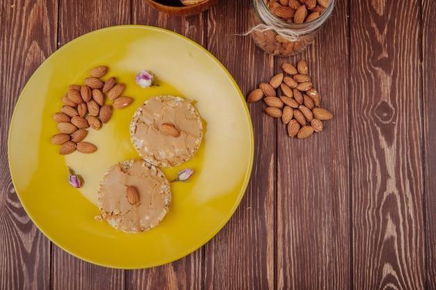 Vista superior de mantequilla de maní con almendras en crujientes galletas de arroz en un plato de cerámica amarilla con almendras dispersas sobre fondo de madera