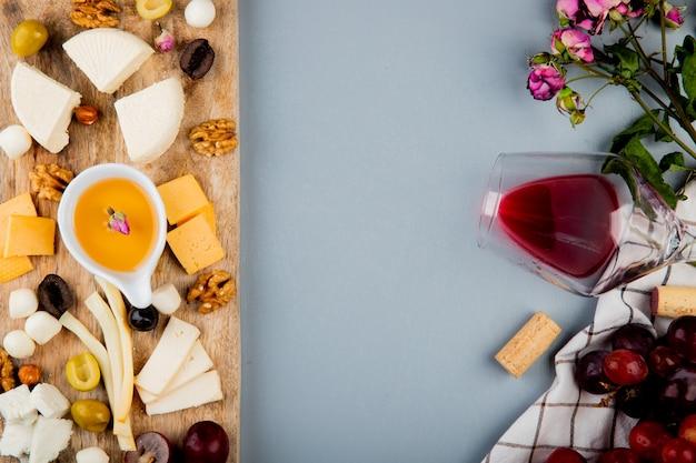 Vista superior de mantequilla con queso uva nueces de oliva en la tabla de cortar y un vaso de corchos de vino flores en blanco con espacio de copia