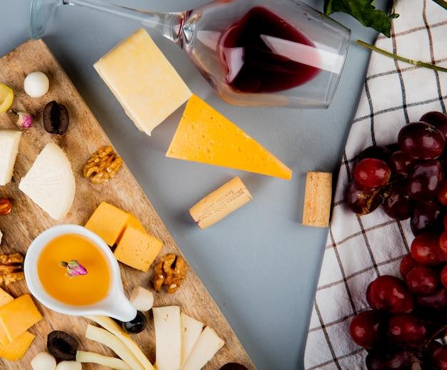 Vista superior de mantequilla con queso uva nueces en tabla de cortar y vaso de corchos de vino en blanco