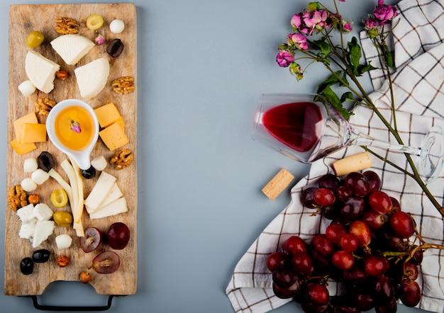 Vista superior de mantequilla con queso uva nueces en tabla de cortar y vaso de corchos de vino flores en blanco