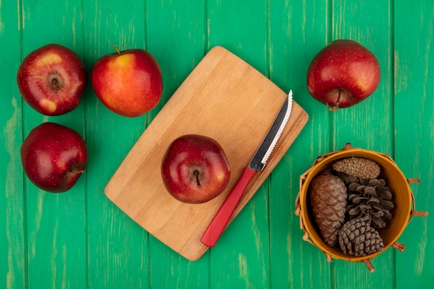 Vista superior de una manzana roja saludable en una tabla de cocina de madera con cuchillo con piñas en un balde con manzanas aislado en una pared de madera verde