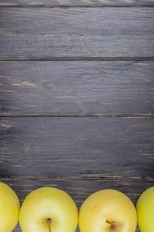Vista superior de manzanas amarillas sobre fondo de madera con espacio de copia