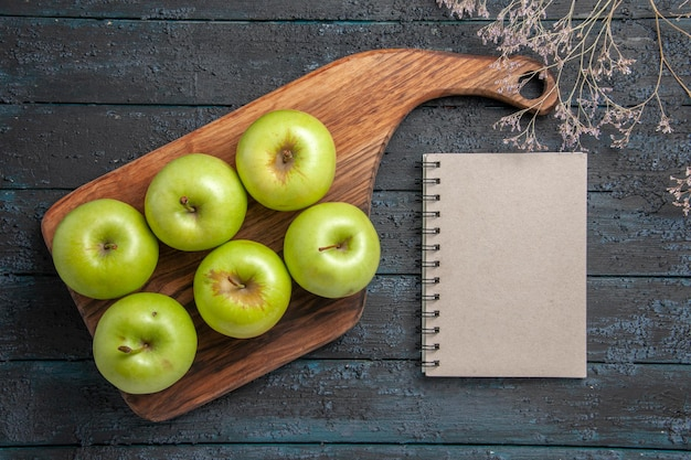 Vista superior de las manzanas a bordo de seis manzanas verdes en el tablero de la cocina junto a las ramas de los árboles y un cuaderno gris sobre una superficie oscura