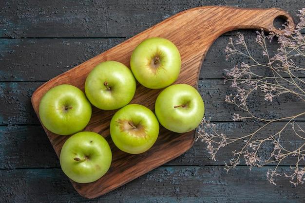 Vista superior de las manzanas a bordo de seis manzanas verdes en el tablero de la cocina junto a las ramas de los árboles en la superficie oscura