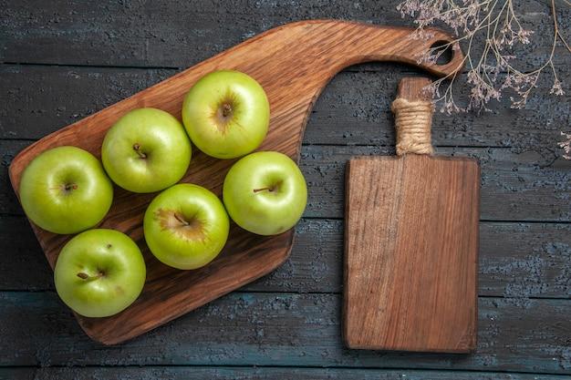 Vista superior de las manzanas a bordo de seis manzanas verdes en el tablero de la cocina junto a las ramas de los árboles y la tabla de cortar en una superficie oscura