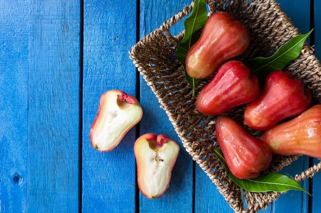 Vista superior de manzanas en la cesta en la mesa de madera azul