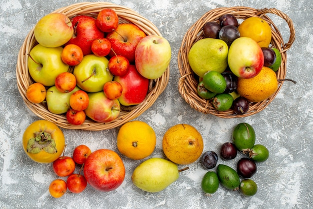 Vista superior manzanas y ciruelas rojas y amarillas feykhoas peras y caquis en las cestas de mimbre y también en el suelo
