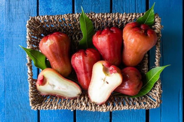 Vista superior de manzanas color de rosa en la cesta en la mesa de madera azul