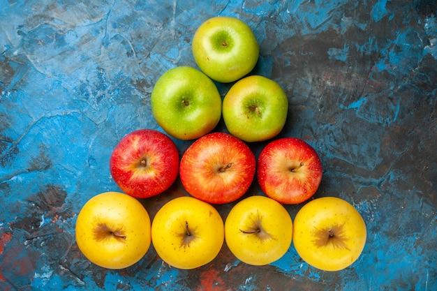 Vista superior de manzanas dulces frescas alineadas como un triángulo sobre fondo azul.