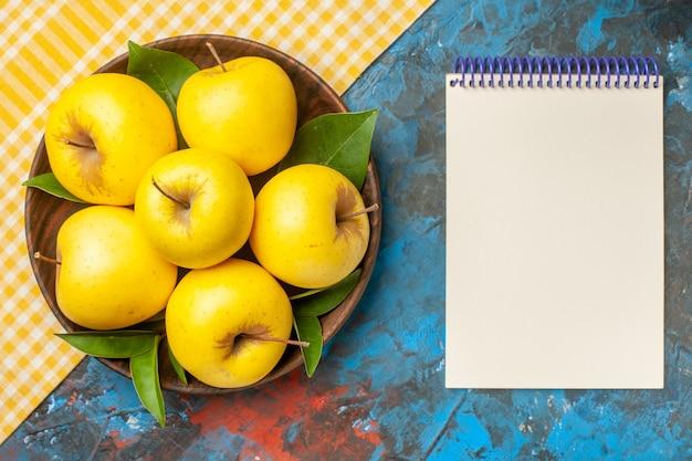 Vista superior de manzanas dulces frescas dentro de la placa sobre fondo azul.