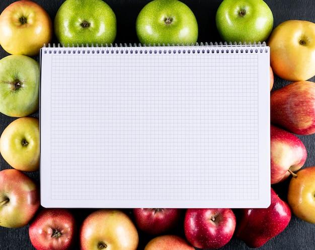 Vista superior de manzanas con espacio de copia en el cuaderno en horizontal de madera negra