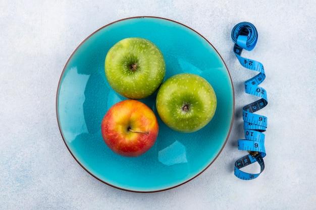 Vista superior de manzanas frescas y coloridas en una placa azul con cinta métrica en blanco