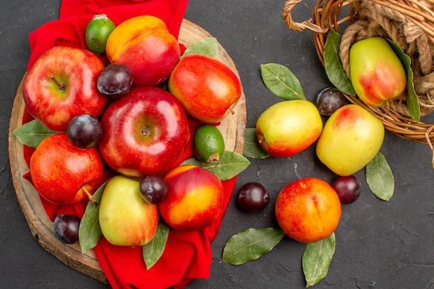 Vista superior de manzanas frescas con melocotones y ciruelas en el árbol de jugo de mesa oscura suave