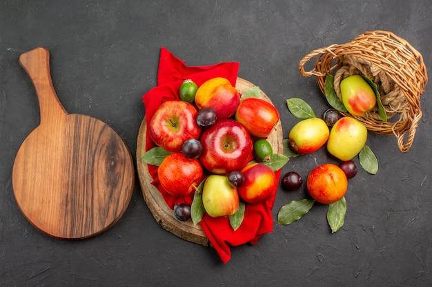 Vista superior de manzanas frescas con melocotones y ciruelas en un jugo maduro de mesa oscura