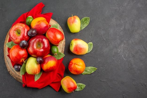 Vista superior de manzanas frescas con melocotones y ciruelas en la mesa gris oscuro árbol de jugo suave maduro