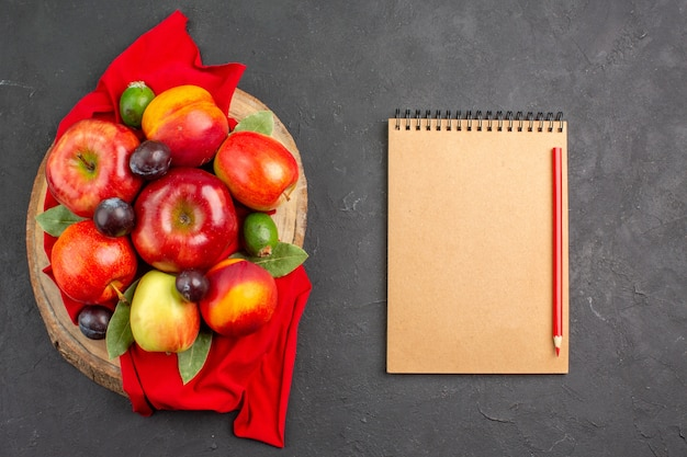 Vista superior de manzanas frescas con melocotones y ciruelas en mesa oscura árbol frutal maduro suave