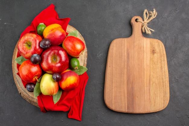 Vista superior de manzanas frescas con melocotones y ciruelas en la mesa oscura jugo suave de árbol maduro