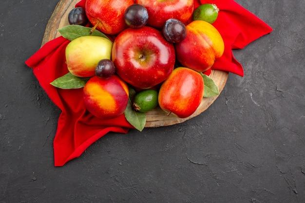 Vista superior de manzanas frescas con melocotones y ciruelas en piso oscuro jugo suave de árboles frutales maduros