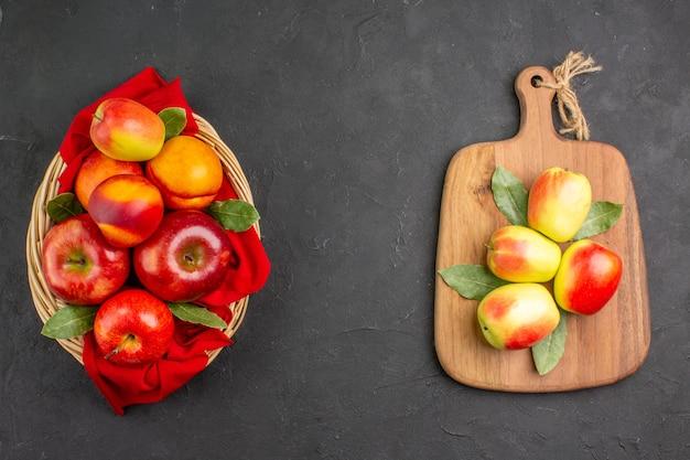 Vista superior de manzanas frescas con melocotones dentro de la canasta en el árbol de fruta fresca de mesa oscura