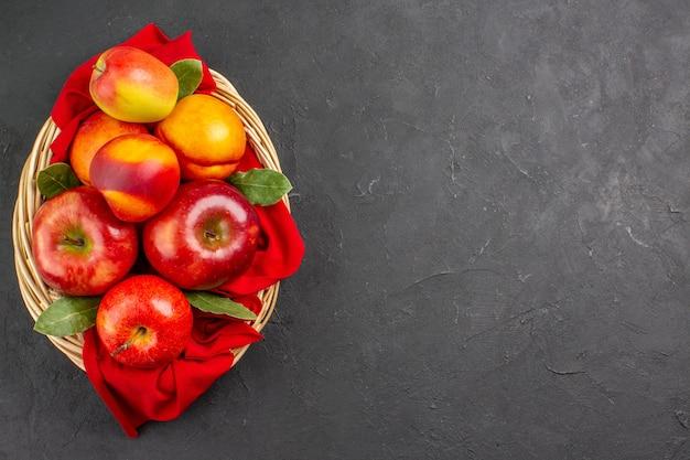 Vista superior de manzanas frescas con melocotones dentro de la canasta en la mesa oscura árbol de fruta fresca madura
