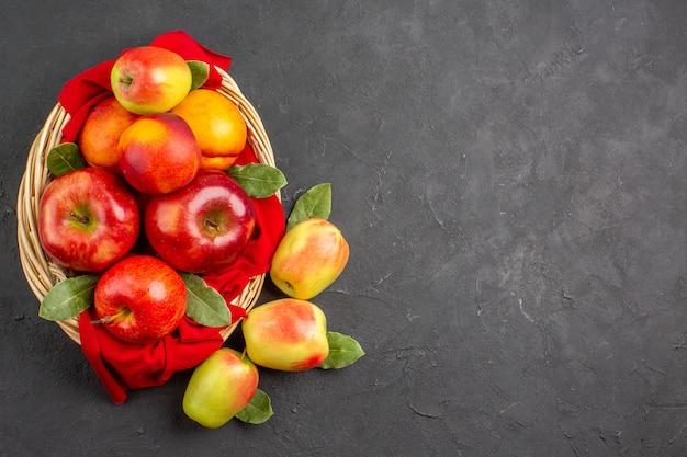 Vista superior de manzanas frescas con melocotones dentro de la canasta en la mesa oscura árbol frutal fresco maduro