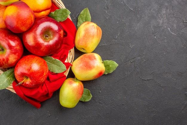 Vista superior de manzanas frescas con melocotones dentro de la canasta en la mesa oscura árbol frutal maduro fresco