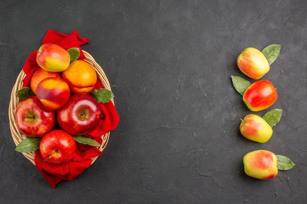 Vista superior de manzanas frescas con melocotones dentro de la canasta en la mesa oscura árboles frutales frescos maduros