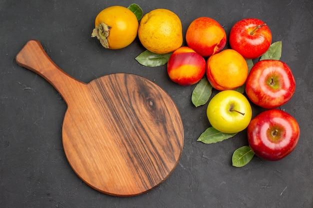 Vista superior de manzanas frescas con otras frutas en el árbol de mesa gris oscuro fresco maduro suave