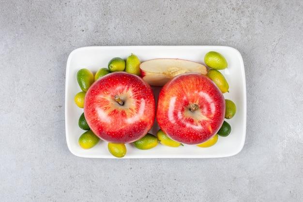Vista superior de manzanas maduras con pila de kumquats en plato blanco.