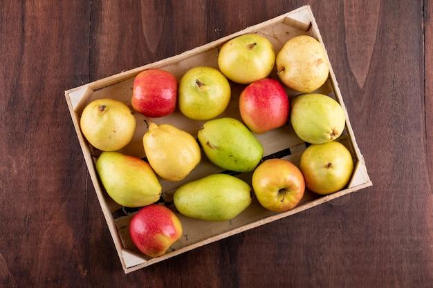 Vista superior de manzanas y peras en caja en horizontal de madera marrón