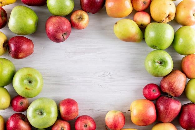 Vista superior de manzanas y peras frutas frescas con espacio de copia en el centro en madera blanca