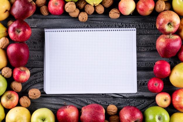 Vista superior de manzanas y peras con nueces y nueces con espacio de copia en el cuaderno en madera gris