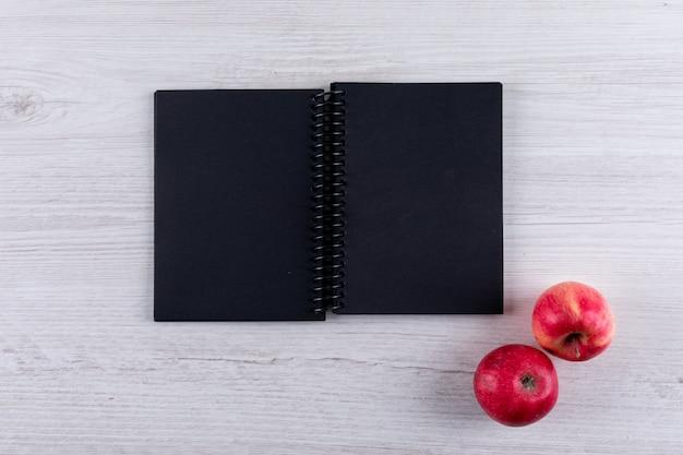 Vista superior de manzanas rojas con espacio de copia en cuaderno negro sobre blanco horizontal de madera