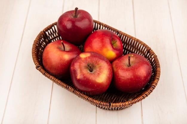 Vista superior de manzanas rojas frescas en un balde en una pared de madera blanca