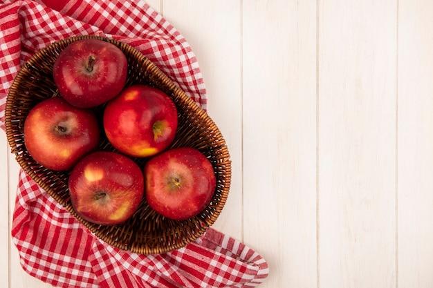 Vista superior de manzanas rojas frescas en un balde sobre un paño de cuadros rojos sobre una pared de madera blanca con espacio de copia
