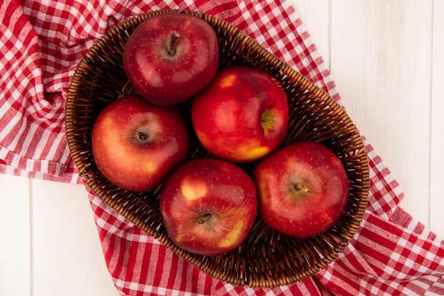 Vista superior de manzanas rojas frescas en un balde sobre un paño de cuadros rojos sobre una pared de madera blanca