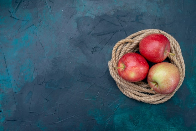 Vista superior de manzanas rojas frescas jugosas y suaves sobre el fondo azul oscuro fruta madura vitamina suave fresca