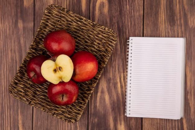 Vista superior de manzanas rojas y jugosas frescas en una bandeja de mimbre en una pared de madera con espacio de copia