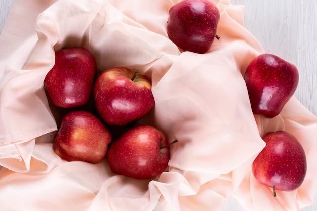 Vista superior manzanas rojas con tela rosa sobre blanco de madera horizontal 1