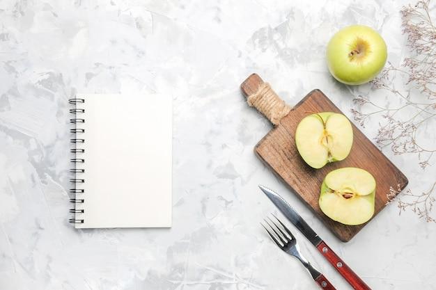 Vista superior de manzanas verdes frescas con bloc de notas sobre fondo blanco.