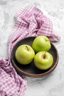 Vista superior de manzanas verdes frescas dentro de la placa sobre fondo blanco.