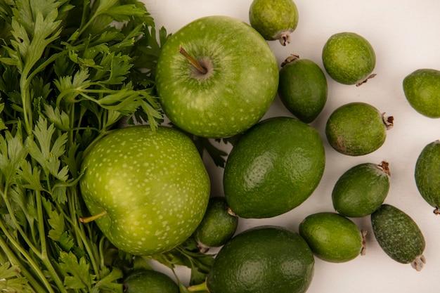 Vista superior de manzanas verdes frescas con limas feijoas y perejil aislado en una pared blanca