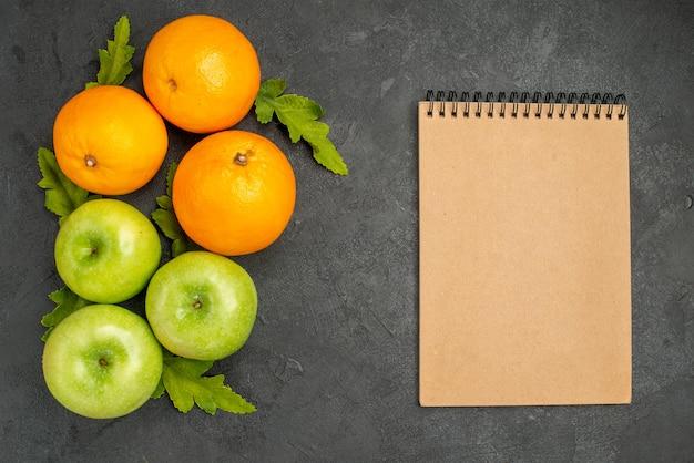 Vista superior de manzanas verdes frescas con naranjas sobre fondo gris