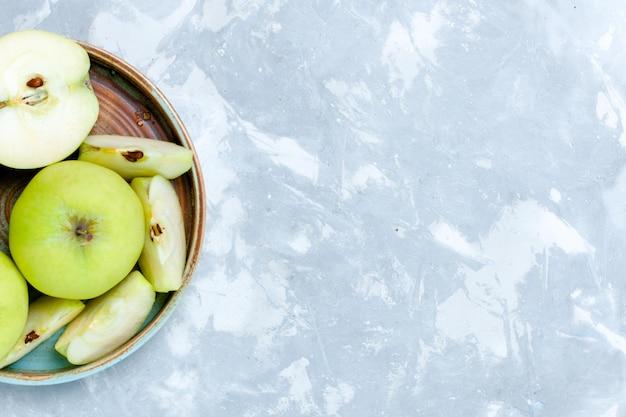 Vista superior de manzanas verdes frescas en rodajas y frutas enteras en la superficie de la luz