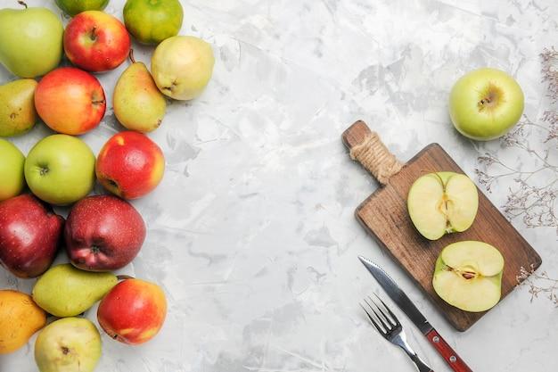 Vista superior de manzanas verdes con otras frutas sobre fondo blanco.