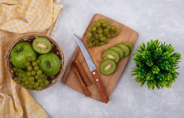 Vista superior de manzanas verdes con uvas verdes y una rodaja de kiwi en una canasta con una toalla a cuadros amarilla y canela con un cuchillo sobre una tabla de cortar sobre un fondo blanco.