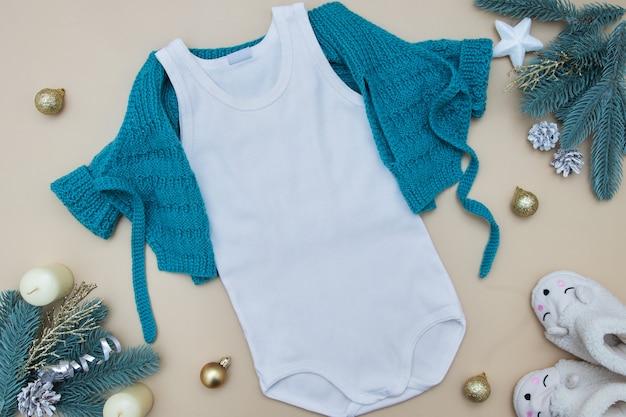 Vista superior maqueta de camiseta blanca para niños con suéter en color con adornos navideños