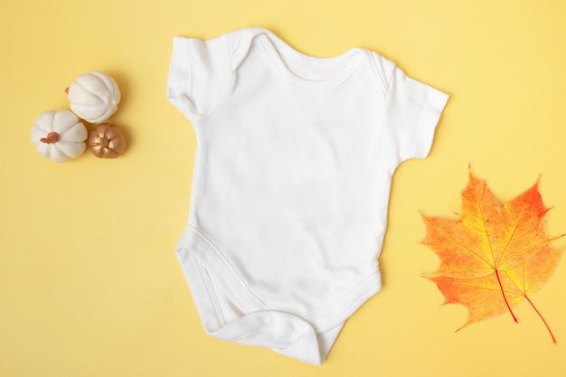 Vista superior de la maqueta del clobodysuit del bebé con calabazas y hojas de arce sobre fondo amarillo para su texto o logotipo en la temporada de otoño